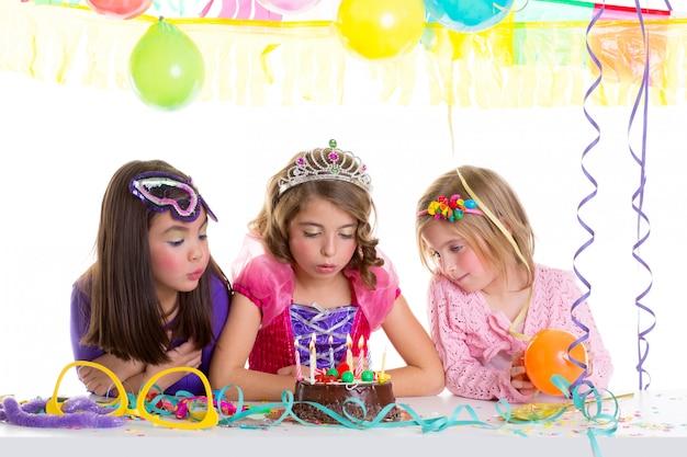Crianças meninas felizes soprando bolo de festa de aniversário