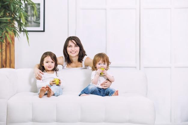 Crianças meninas lindas fofas com a mãe em casa juntas comendo maçãs naturais