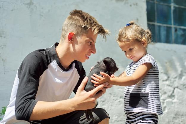 Crianças menino adolescente e menina da criança com porco preto recém-nascido na fazenda.