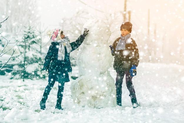 Crianças, menino e menina, ao ar livre no inverno nevado estão fazendo um grande boneco de neve