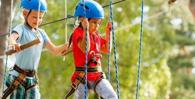 Crianças, menino e uma menina no parque de corda passam obstáculos. irmão e irmã escalam a estrada de corda