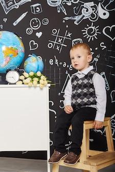 Crianças menino estudante estuda na escola primeiro de setembro, último dia de estudo, troca entre as aulas. as crianças da escola primária descansam. os alunos sentam-se na sala de aula. rússia, sverdlovsk, 1º de setembro de 2018