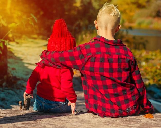 Crianças menino menina sentam-se juntos com as costas no outono em vermelho em um abraço, irmão, irmã
