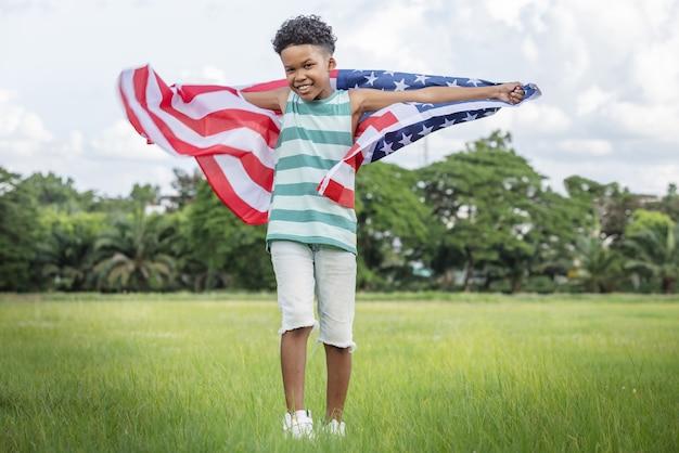 Crianças menino segurando uma bandeira americana dos eua correndo