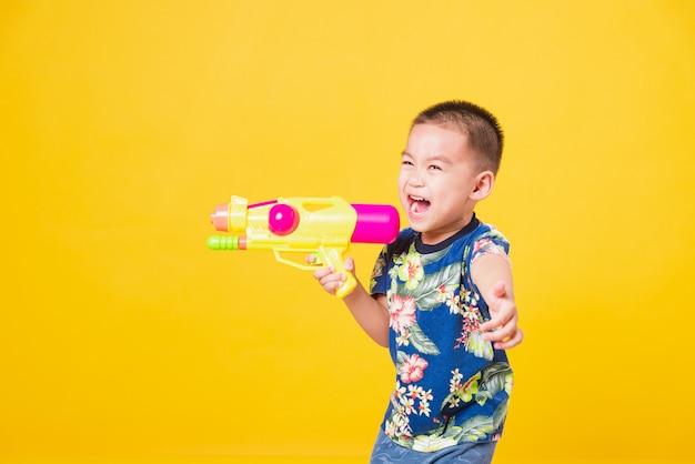 Crianças menino sorrindo em pé tão feliz vestindo uma camisa de flor no dia do festival songkran segurando uma pistola d'água