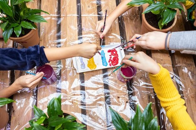 Crianças mergulhando a placa de pintura com uma vista superior do pincel