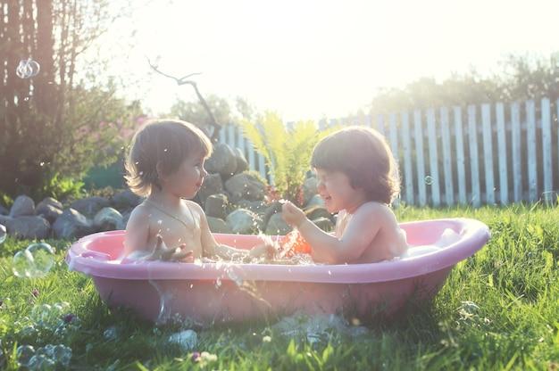 Crianças na água do banho ao ar livre