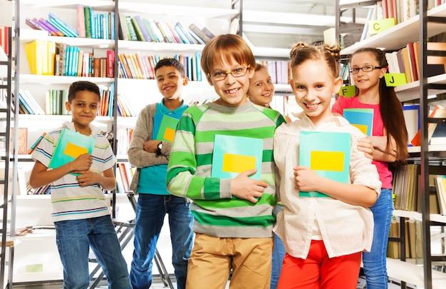 Crianças na biblioteca segurando cadernos e de pé entre as estantes