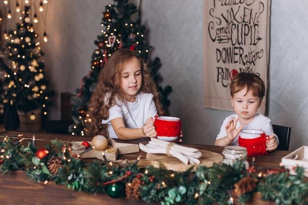 Crianças na decoração de natal com chá em casa aconchegante com luzes coloridas do ano novo