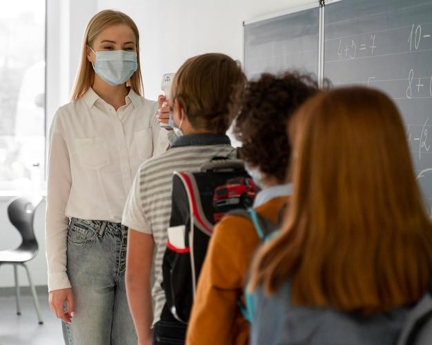 Crianças na escola alinhadas para verificação de temperatura por professora