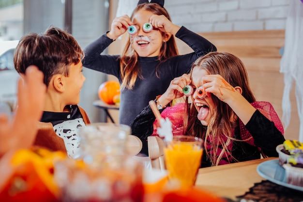 Crianças na festa. três crianças radiantes com rostos pintados de cores vivas usando fantasias na festa de halloween Foto Premium