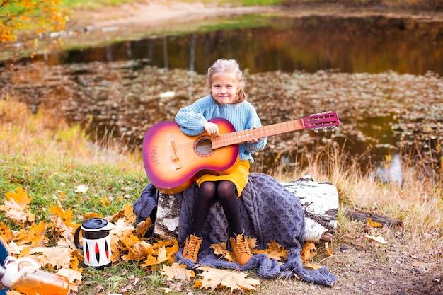 Crianças na floresta de outono em um piquenique grelha salsichas e tocam violão