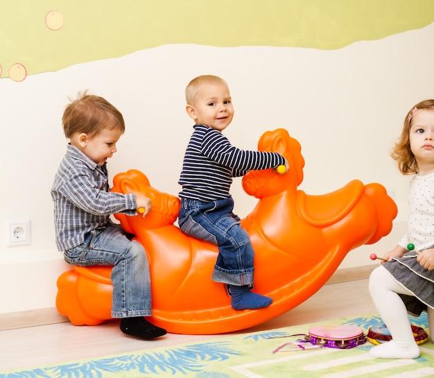 Crianças na gangorra de plástico de balanço na sala interna