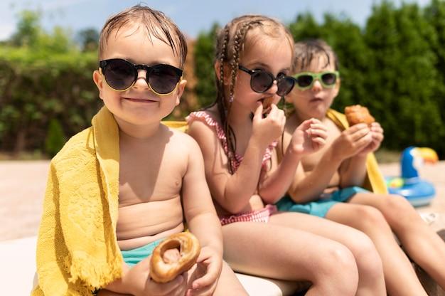 Crianças na piscina comendo