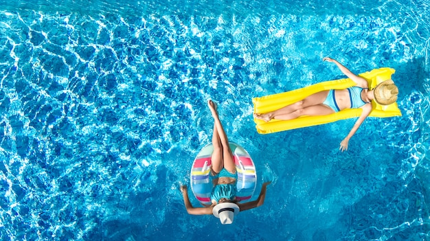 Crianças na piscina zangão aéreo vista fom acima, crianças felizes nadam no anel inflável anel e colchão, meninas ativas se divertem na água em férias em família no resort de férias