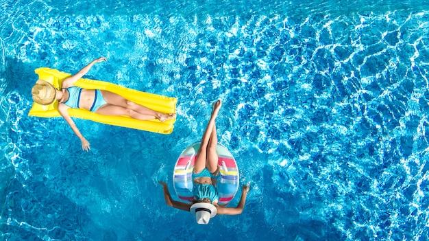 Crianças na piscina zangão aéreo vista fom acima, crianças felizes nadam no anel inflável donut e colchão, meninas ativas se divertem na água em férias em família no resort de férias