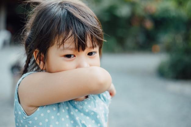 Crianças na postura de tosse do cotovelo, que é espirros correto.