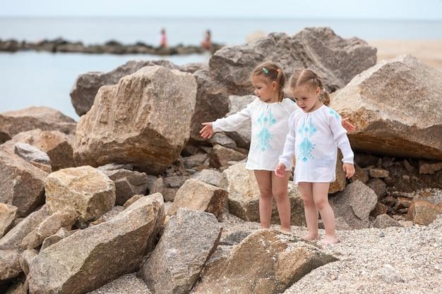 Crianças na praia do mar. gêmeos de pé contra pedras e água do mar.