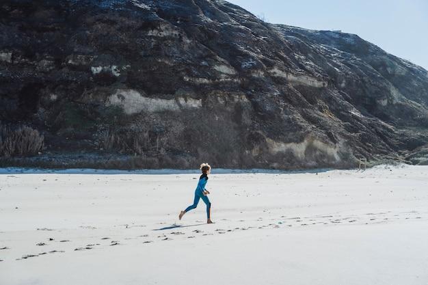 Crianças na praia, no oceano, jogging antes de surfar