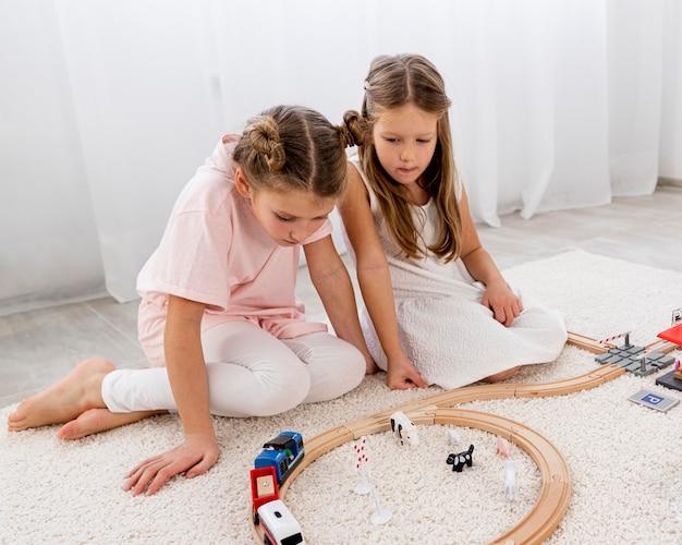 Crianças não binárias brincando com jogos de carros dentro de casa