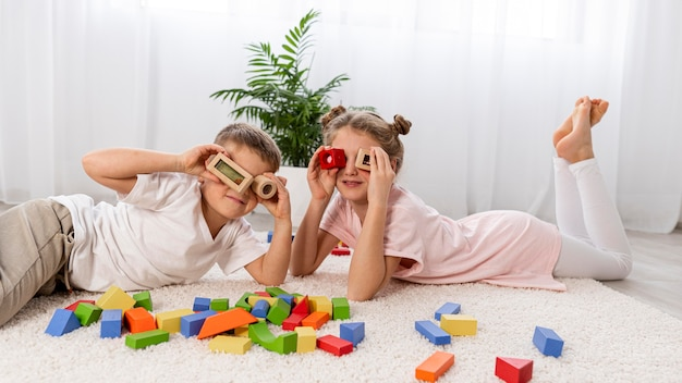 Crianças não binárias brincando com um jogo colorido em casa