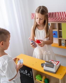 Crianças não binárias brincando dentro de casa