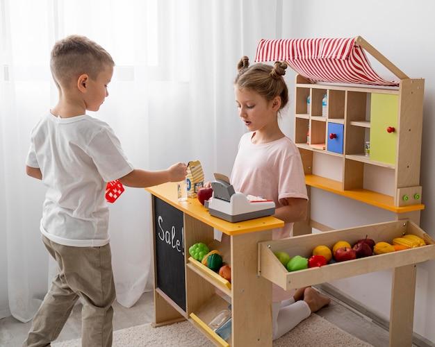 Crianças não binárias brincando juntas dentro de casa