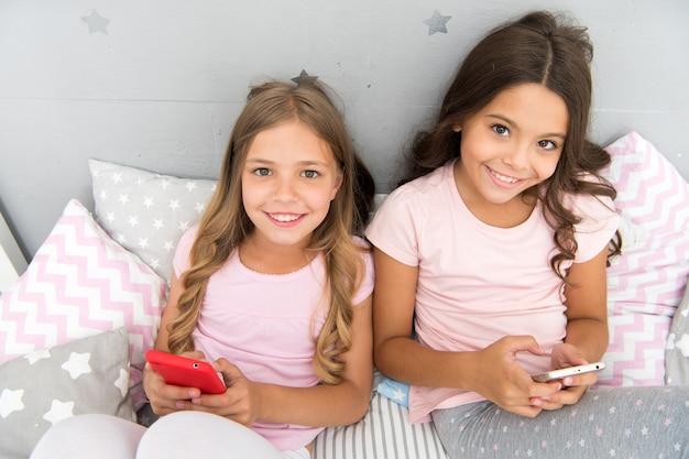 Crianças navegando em redes sociais de aplicativos móveis na internet. crianças modernas que vivem telefones celulares de vida online. viciado em celulares. menina joga jogos smartphone online. conceito de festa do pijama. infância feliz.