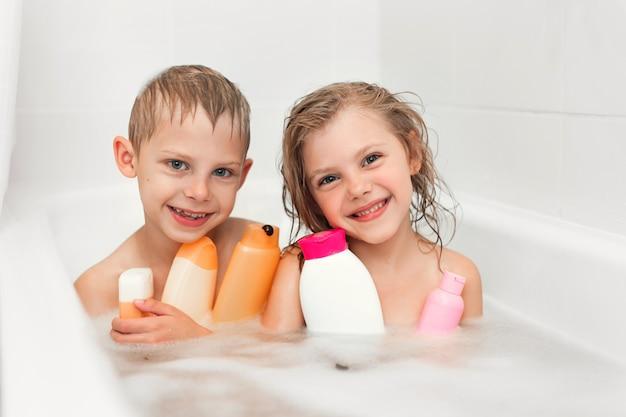 Crianças no banho, muitas bolhas e um frasco de xampu nas mãos