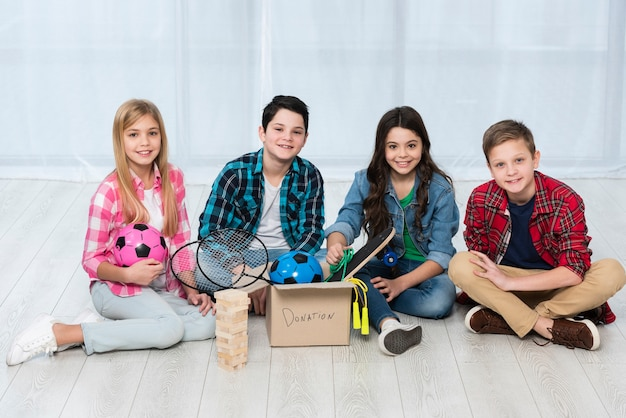 Crianças no chão com caixa de doação