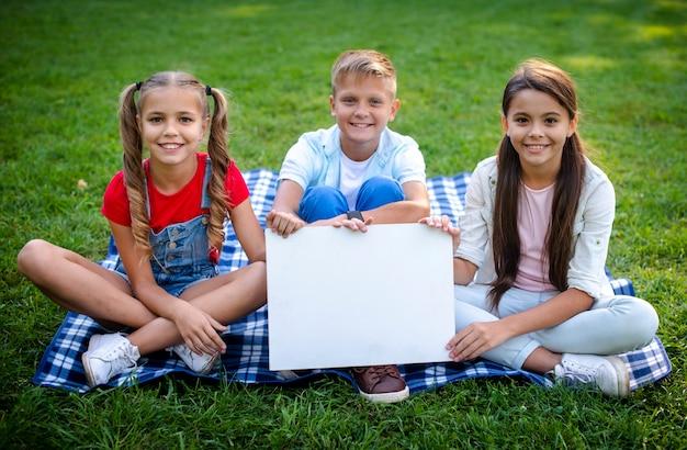 Crianças no cobertor, segurando um cartaz nas mãos