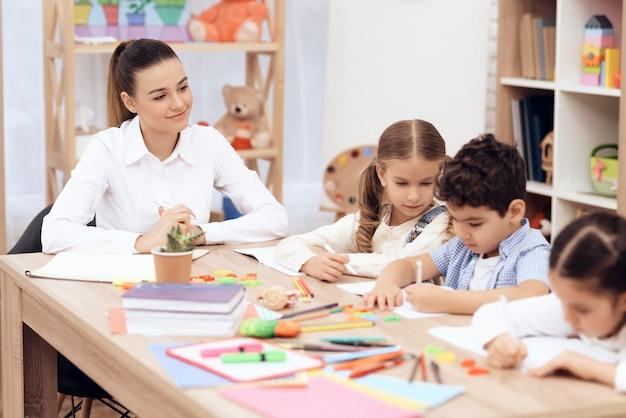Crianças no jardim de infância aprendem a desenhar com lápis.