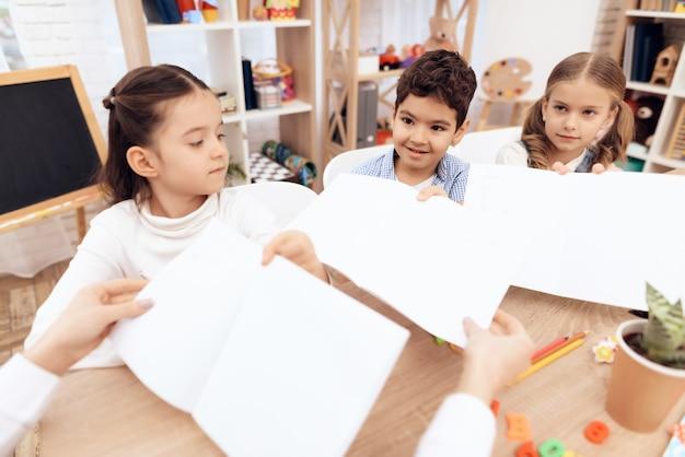 Crianças no jardim de infância mostram seus desenhos.
