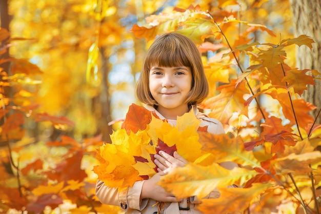 Crianças no parque com folhas de outono. foco seletivo.