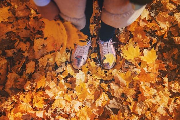 Crianças no parque com folhas de outono nos sapatos. foco seletivo.