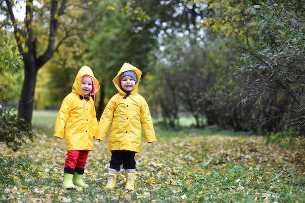 Crianças no parque de outono andam em capas de chuva durante o dia