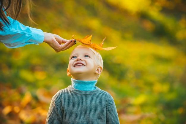 Crianças no parque outono em fundo de folha amarela.