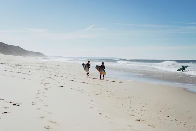 Crianças no surf. nazare, portugal. crianças e adolescentes em placas de surf de roupa de banho.