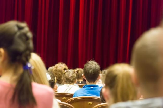 Crianças no teatro ou cinema antes do espetáculo.