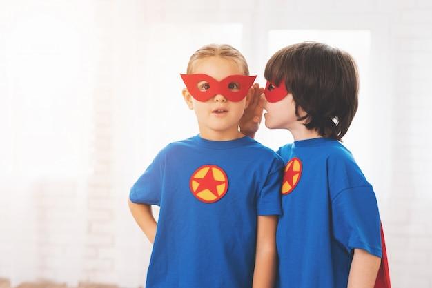 Crianças nos ternos vermelhos e azuis dos super-heróis.