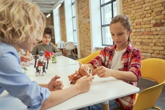 Crianças observadoras com pensamento independente, sentadas à mesa examinando brinquedos técnicos enquanto