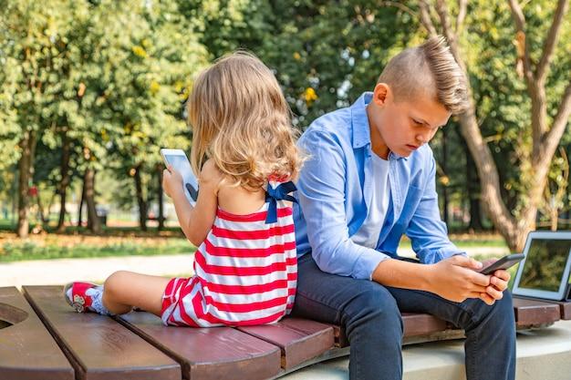 Crianças ocupadas olhando para seus telefones, mandando sms e brincando sentadas do lado de fora