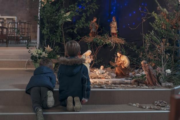 Crianças olham para o presépio de natal com josé maria e o pequeno jesus em um berço
