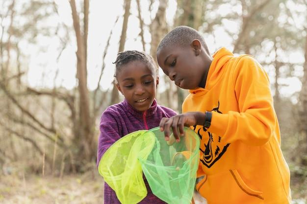 Crianças olhando através de suas redes de pesca