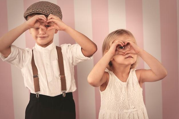 Crianças olhando através do formato do coração com as mãos