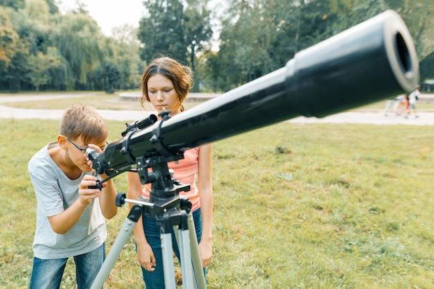 Crianças olhando com interesse em um telescópio para o céu