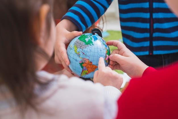 Crianças olhando e aprendendo o globo