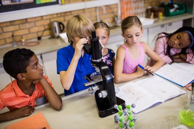 Crianças olhando no microscópio