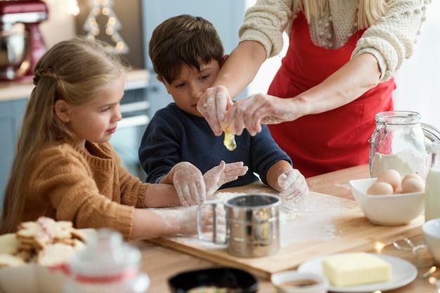 Crianças olhando para ovo quebrado pela mãe