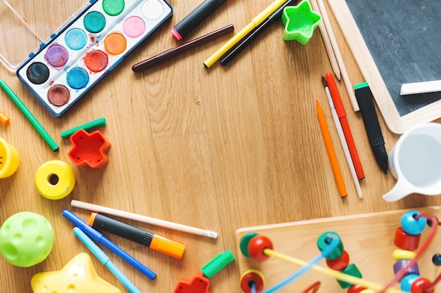 Crianças ou conceito de crianças. brincar de brinquedos e desenhar materiais em cima da mesa. vista de cima.